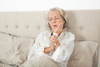Senior woman suffering from toothache resting in bed