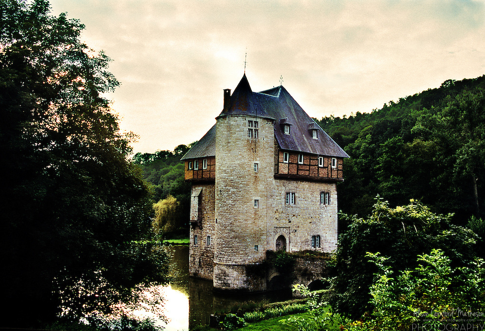 The sun sets on Crupet castle (Château de Crupet, also known as the Château des Carondelet) surrounded by a moat in the Wallonian region of Belgium.