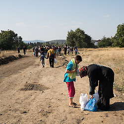 Refugees make their way to the Macedonian reception center near the town of Gevgelija on August 25, 2015.  After crossing into Macedonia the refugees travel north to border with Serbia where they will continue their journey to other European states.