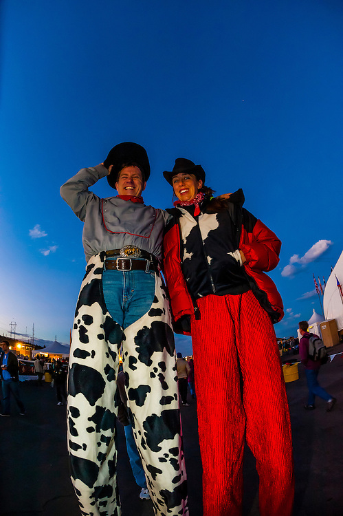 A man and woman on stilts, Balloon FIesta Park during the Albuquerque International Balloon Fiesta, Albuquerque, New Mexico USA.