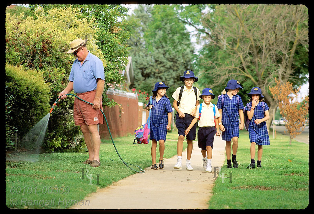 Girls & boys walk together to school past man watering his lawn in early morn; Wagga Wagga, NSW. Australia