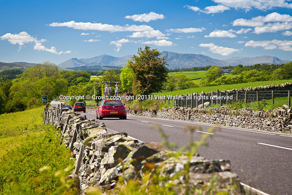 Car on A5 road near Pentrefoelas with Moel Siabod and Snowdon in background<br /> Conwy County<br /> North<br /> Road<br /> Transport