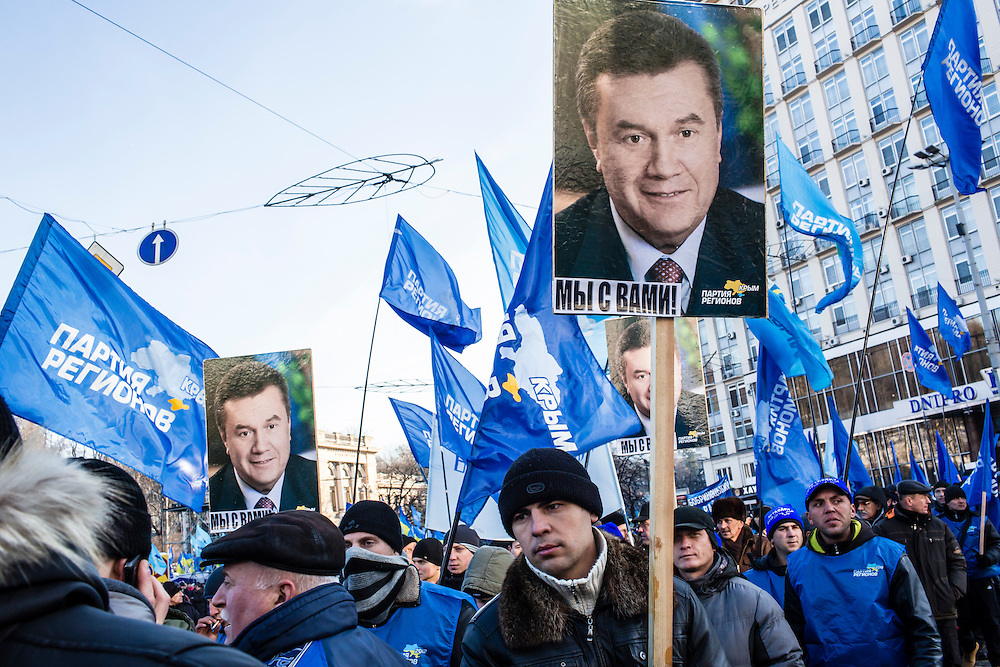 KIEV, UKRAINE - DECEMBER 14: Men carry signs with the face of Ukrainian President Viktor Yanukovych at a pro-government rally on December 14, 2013 in Kiev, Ukraine. Thousands of people have been protesting against the government since a decision by President Yanukovych to suspend a trade and partnership agreement with the European Union in favor of incentives from Russia. (Photo by Brendan Hoffman/Getty Images)