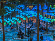 """Luminaries"" an interactive light installation at Winter Garden in Battery Park City. Inspired by the season's traditions of sharing, community, and connection, Luminaries immerses visitors in a canopy of light emanating from 650 hanging lanterns. Visitors can send a wish to the lanterns by touching a Wishing Station, transforming the intallation into a mesmerizing display of chanching lights."