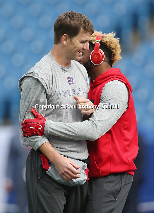New York Giants quarterback Eli Manning (10) (left) smiles as he gets a hug from New York Giants wide receiver Odell Beckham Jr. (13) while warming up before the 2015 NFL week 4 regular season football game against the Buffalo Bills on Sunday, Oct. 4, 2015 in Orchard Park, N.Y. (©Paul Anthony Spinelli)