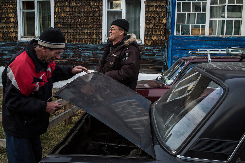 Men stand around and talk on Wednesday, October 23, 2013 in Vydrino, Russia.