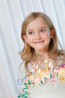 Happy young girl looking away with candles burning on birthday cake