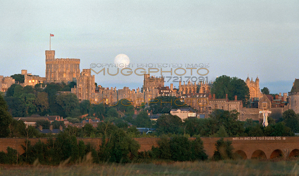 A full moon rises over Windsor Castle at sunset.