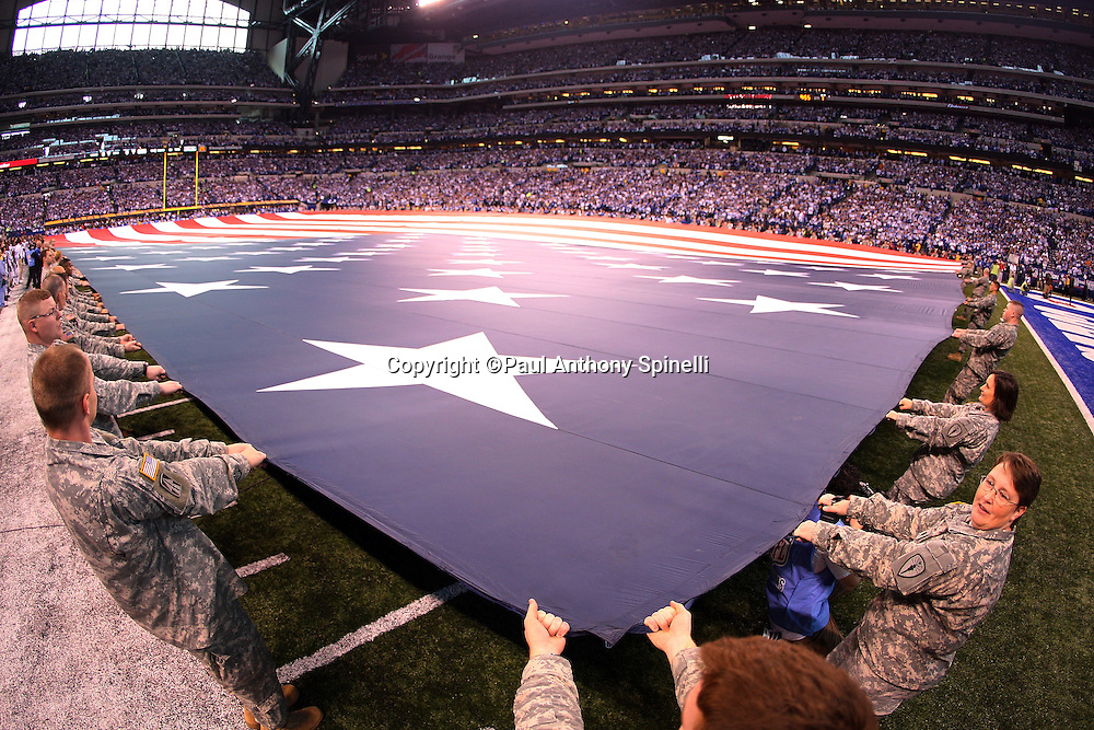 Members of the U.S. Military hold a large American flag during the singing of the National Anthem prior to the Indianapolis Colts AFC Championship football game against the New York Jets, January 24, 2010 in Indianapolis, Indiana. The Colts won the game 30-17. ©Paul Anthony Spinelli