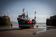 A man walks his dog around Opportunity (FE 6) a Folkestone registered Fishing boats sit on the sand in a dry harbour entrance  due to the tide being out, waiting for the tide to come back in. Folkestone Harbour, Kent, United Kingdom. (photo by Andrew Aitchison / In pictures via Getty Images)
