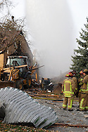 Firefighters from several departments, including Fairborn and Wright-Patterson AFB at the scene of what appears to be a gas-line explosion on Wayne Drive in Fairborn, Saturday, November 12, 2011. The explosion damaged at least three houses, the house behind the damaged backhoe was destroyed, the house to its left has a hole in the wall..