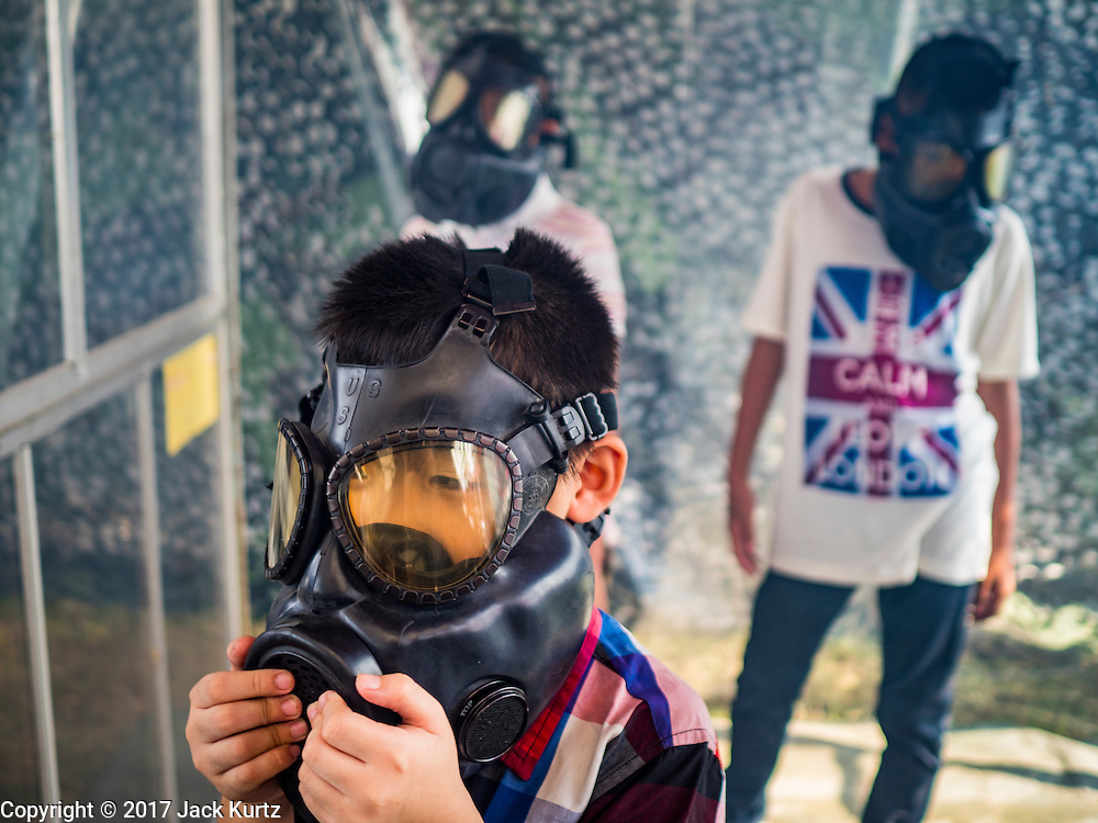 """14 JANUARY 2017 - BANGKOK, THAILAND: Thai children wear gas masks in a demonstration of gas masks during Children's Day activities at the King's Guard, 2nd Cavalry Division base in Bangkok. Thailand National Children's Day is celebrated on the second Saturday in January. Known as """"Wan Dek"""" in Thailand, Children's Day is celebrated to give children the opportunity to have fun and to create awareness about their significant role towards the development of the country. Many government offices open to tours and military bases hold special children's day events. It was established as a holiday in 1955.       PHOTO BY JACK KURTZ"""