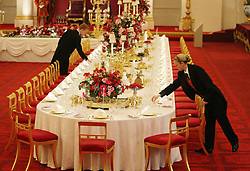 Staff members lay the State Banquet table, in the ballroom at Buckingham Palace, London, ahead of the summer opening of the royal house to the public.