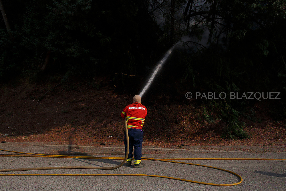 LEIRIA, PORTUGAL - JUNE 19:  A fireman works on a forest fire after a wildfire took dozens of lives on June 19, 2017 near Pedrogao Grande, in Leiria district, Portugal. On Saturday night, a forest fire became uncontrollable in the Leiria district, killing at least 62 people and leaving many injured. Some of the victims died inside their cars as they tried to flee the area.  (Photo by Pablo Blazquez Dominguez/Getty Images)