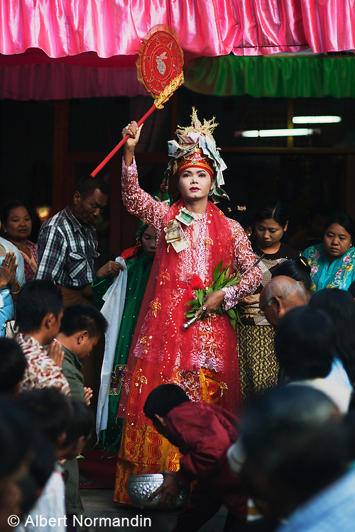 Ladyboy in full festival dress with worshipping crowd in procession at Mount Popa Nat Festival