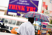 A man holding an umbrella walks near a sign promoting tuberculosis awareness in central Accra, Ghana on Tuesday June 16, 2009.