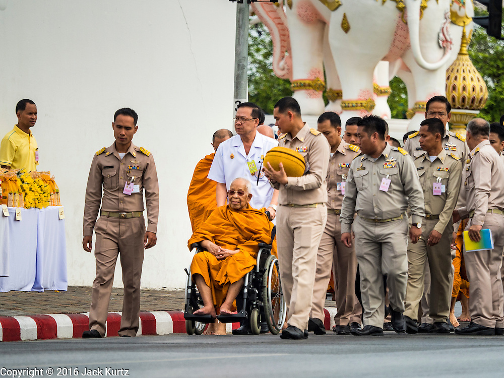 09 JUNE 2016 - BANGKOK, THAILAND:  An elderly Buddhist monk in a wheelchair at a special alms giving ceremony at the Grand Palace. Thailand marked 70 years of the reign of Bhumibol Adulyadej, the King of Thailand, with a special alms giving ceremony for 770 monks in front of the Grand Palace in Bangkok. The King, also known as Rama IX, ascended the throne on 9 June 1946. He is the longest serving monarch in Thai history and the longest serving monarch in the world today. He is revered by most Thais and is widely seen as a unifying figure in the country.    PHOTO BY JACK KURTZ
