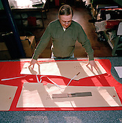 A tailor cuts red material for flying suits of of the elite 'Red Arrows', Britain's prestigious Royal Air Force aerobatic team. The man is a bespoke tailor at Dale Techniche, Nelson, Lancashire. Every Winter, the Red Arrows place about 40 pilot suit orders and 180 blue (support ground crew) suits. Tricia adjusts her thread while the suit is complete on her work bench. The clothing factory also designs the Red Arrows badges, each requiring 15,000 stitches. All suits are made from Nomex by the Du Pont corporation, containing 5% Kevlar. Flame-retardant, they fit exactly each team member. Fouteen different measurements are taken before the first suit is cut, each one requiring approximately three metres of dyed cloth. When a suit is complete, each one is signed inside by the machinist.