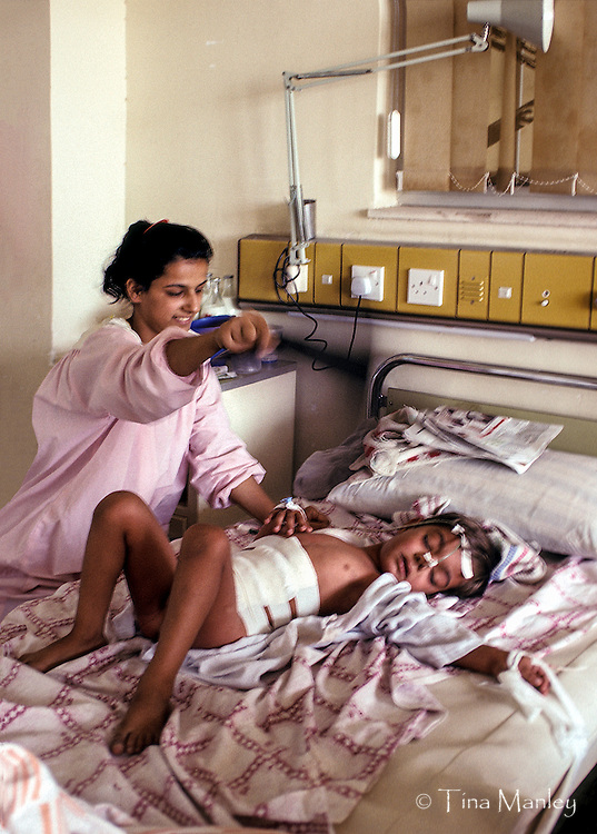 IRAQ, BAGHDAD:<br /> SADDAM CHILDREN'S TEACHING HOSPITAL,<br /> MOTHER FANNING CHILD WITH X-RAY, APPENDECTOMY WITHOUT ANESTHESIA