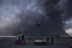 October 21, 2016 - Qayyarah, Iraqi-Kurdistan, Iraq - Smoke from the burning Qayyarah oilfields blots out the sky above an Iraqi Army checkpoint near the town of  Qayyarah, Iraq. The oilfields, which surround the town, were set alight by Islamic State militants as they retreated from Iraqi forces in July 2016...Since being retaken from the Islamic State the town of Qayyarah has become an important staging post for the Iraqi Army, and some US support elements, in the buildup to the Mosul offensive. (Credit Image: © Matt Cetti-Roberts/London News Pictures via ZUMA Wire)