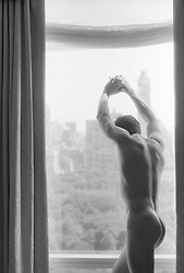 naked man looking out a picture window over Central Park, New York