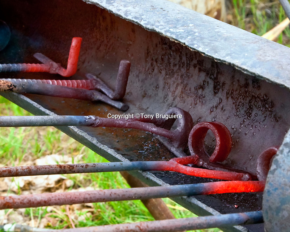 Branding irons are being heated by a propane flame. The brand is a mark of ownership of the cattle in case they stray or are stolen.