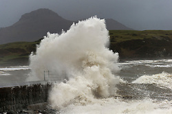 © Licensed to London News Pictures. 29/01/2016. Criccieth, Gwynedd, Wales, UK. Huge waves crash against a breakwater against a backdrop of Snowdonia National Park. Gale force winds batter the North Wales seaside resort of Criccieth in Gwynedd, Wales, last night and this morning. Photo credit: Graham M. Lawrence/LNP