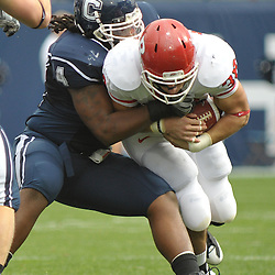 Oct 31, 2009; East Hartford, CT, USA; Connecticut defensive tackle Twyon Martin (4) tackles Rutgers running back Joe Martinek (38) during first half Big East NCAA football action between Rutgers and Connecticut at Rentschler Field.
