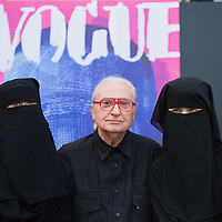 "VENICE, ITALY - JUNE 01:  Cretaor of fashion magazines and artisit Flavio Lucchini poses with two models in front of his work ""poster/vogue"" part of the exhibition ""What Women Want (?)"" on June 1, 2011 in Venice, Italy. The exhibition addresses the controversiat theme of the burqa"