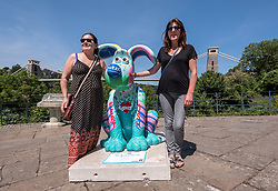 "© Licensed to London News Pictures.  02/07/2018; Bristol, UK. Gromit Unleashed 2. People pose with the  ""The Bristol Hound"" Gromit character installed at Sion Hill by the Clifton Suspension Bridge for the Gromit Unleashed 2 sculpture trail. Gromit Unleashed 2, which officially begins on 02 July, will see the Academy Award®-winning character Gromit by Nick Park at Aardman Animations returning to Bristol in 2018 for the second time on sculpture trails to raise money for  the Grand Appeal charity. The character of Gromit will be joined by Wallace and their arch nemesis Feathers McGraw. The trail will feature over 60 giant sculptures designed by high-profile artists, designers, innovators and local talent. Sculptures will be positioned in high footfall and iconic locations around Bristol and the surrounding area. Photo credit: Simon Chapman/LNP"