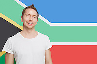 Portrait of young Caucasian man smiling against South African flag