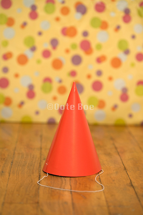 a red paper party hat on a wooden floor
