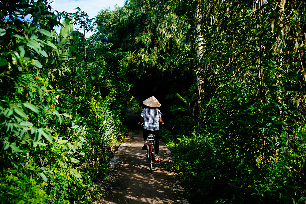 A woman rides a bicycle through a small village backroad in the Mekong Delta in southern Vietnam.