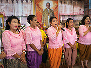 02 DECEMBER 2014 - BANGKOK, THAILAND: Thai women sing a traditional Thai song to honor the King (in portrait behind them) before the Trooping of the Colors in Bangkok. The Thai Royal Guards parade, also known as Trooping of the Colors, occurs every December 2 in celebration of the birthday of Bhumibol Adulyadej, the King of Thailand. The Royal Guards of the Royal Thai Armed Forces perform a military parade and pledge loyalty to the monarch. Historically, the venue has been the Royal Plaza in front of the Dusit Palace and the Ananta Samakhom Throne Hall. This year it was held on Sanam Luang in front of the Grand Palace.    PHOTO BY JACK KURTZ