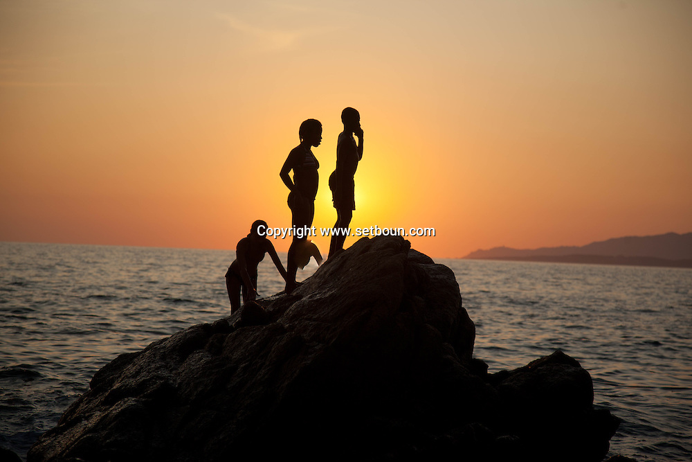 Corsica, Propriano area, Arena Bianca beach. young people and children diving in the mediterranean sea at sunset,