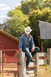 cowboy on a ranch sitting on a fence