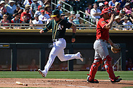 MESA, AZ - MARCH 09:  Tyler Ladendorf #25 of the Oakland Athletics scores behind Stuart Turner #74 of the Cincinnati Reds in the second inning of the spring training game at HoHoKam Stadium on March 9, 2017 in Mesa, Arizona.  (Photo by Jennifer Stewart/Getty Images)