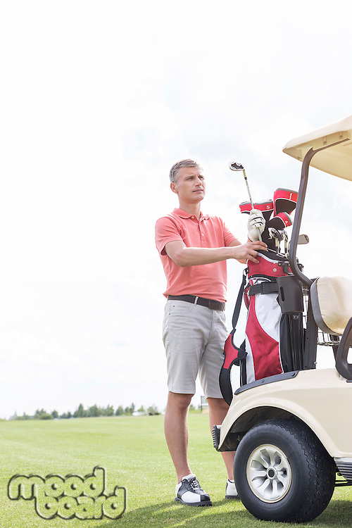 Middle-aged man standing by cart at golf course