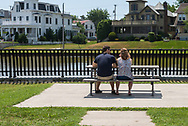 Asbury Park, NJ USA --June 18, 2017 --  A couple sits at a picnic table overlooking a lake in Asbury Park, NJ. Editorial Use Only