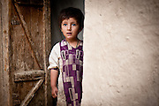 An Afghan child looks out from a doorway while American and Afghan soldiers search his family's compound in Nur Mohammad Kalache.