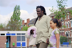 Single father walking across primary school playground holding hands with young daughter,