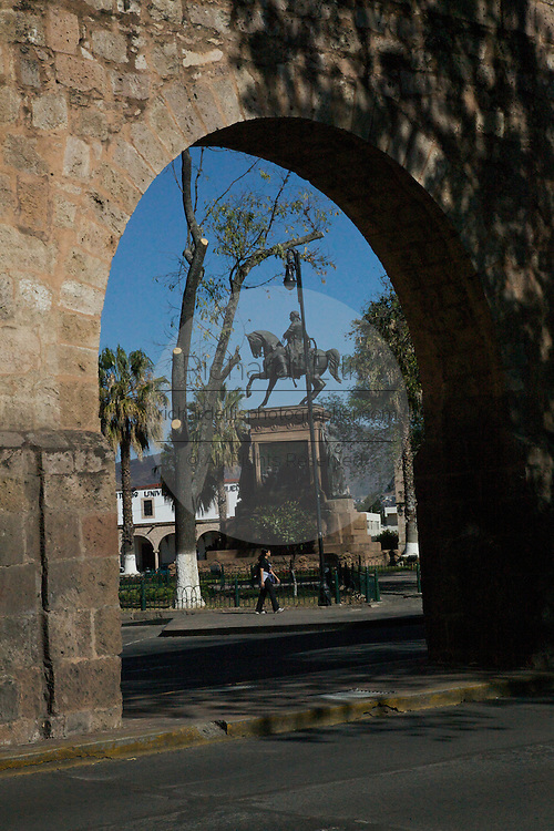 View of Estatua Ecuestre al Patriota Morelos, a statue honoring Jose Maria Morelos y Pavon, local hero and a key figure in Mexican Independence and whom the town is named after in Plaza Morelos, Morelia, Mexico as seen through the cities ancient Aqueduct. The city is a UNESCO World Heritage Site and hosts on of the best preserved collection of Spanish Colonial architecture in the world.