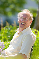 A Senior Adult, happily immersed in his garden smiles for the camera during a break.  Qualicum Beach, Vancouver Island, British Columbia, Canada.