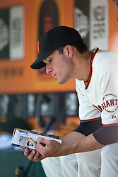 SAN FRANCISCO, CA - MAY 14:  Javier Lopez #49 of the San Francisco Giants reads the Atlanta Braves media guide in the dugout during the first inning at AT&T Park on May 14, 2014 in San Francisco, California.  The San Francisco Giants defeated the Atlanta Braves 10-4.  (Photo by Jason O. Watson/Getty Images) *** Local Caption *** Javier Lopez