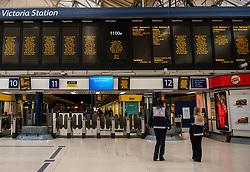 © Licensed to London News Pictures. 28/04/2020. London, UK. Staff at Victoria Station in Westminster stop for the 1 minute silence next to the train barriers. UK holds a minute silence for key workers who have died in the Coronavirus pandemic as the Office for National Statistics reveals there were 1000s of more deaths due to Covid-19 outside of hospitals as the coronavirus pandemic crisis continues. Photo credit: Alex Lentati/LNP