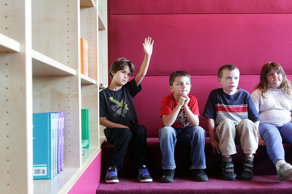Kade Morrison, second grader, raises his hand in the soundproof area of the new library. Vernonia is rebuilding from vicious floods, and the new school has been built above the flood zone.