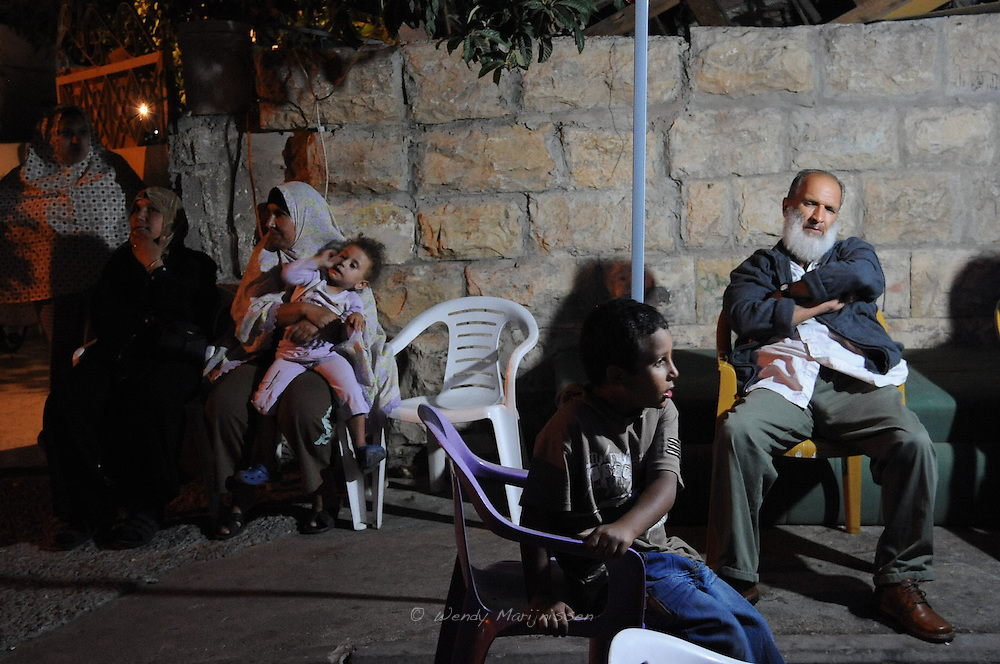 Neighbours and members of the Ghawi family sit outside the former home of the family.The family were forcefully evicted from their home on the 2nd of August 2009 and are now living and sleeping outside on the street. Sheikh Jarrah, Jerusalem, Israel