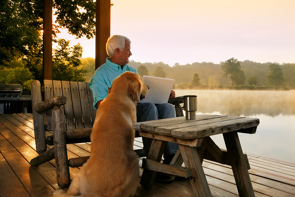 Man on lakeside deck with dog