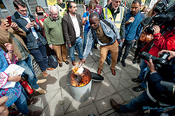 Pictured: Protesters burn their eviction letters from private firm SERCO.<br /> <br /> Protesters gathered outside the main Home Office building in Glasgow to protest at private company SERCO's attempts to evict failed asylum seekers from their homes.<br /> <br /> © Dave Johnston / EEm
