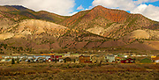 Amtrak Zephyr landscape view, village and mountains, colorful reds, Colorado